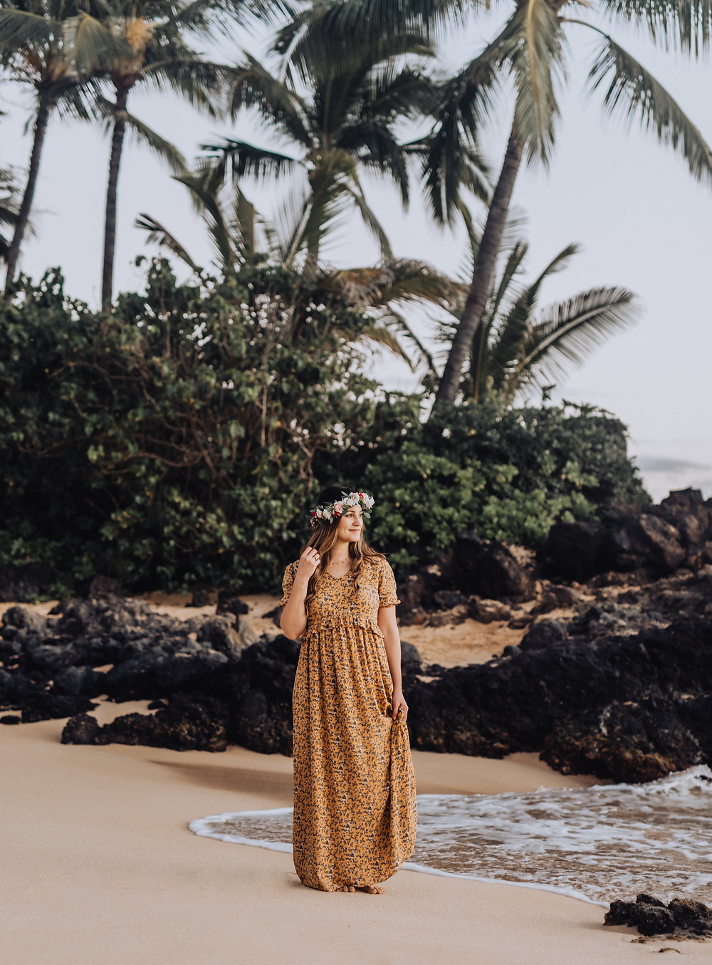 Woman standing on a beach in Maui Hawaii wearing a long mustard dress.