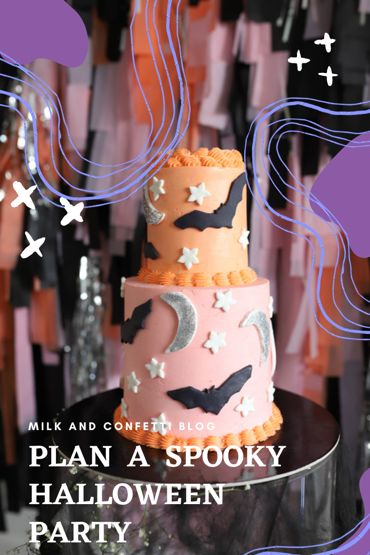 A kids Halloween themed cake decorated with white flowers, flying black bats, silver moon with pink and orange frosting on a small table showcased in front of a wall filled with pink, orange, black and silver sparkly streamers.