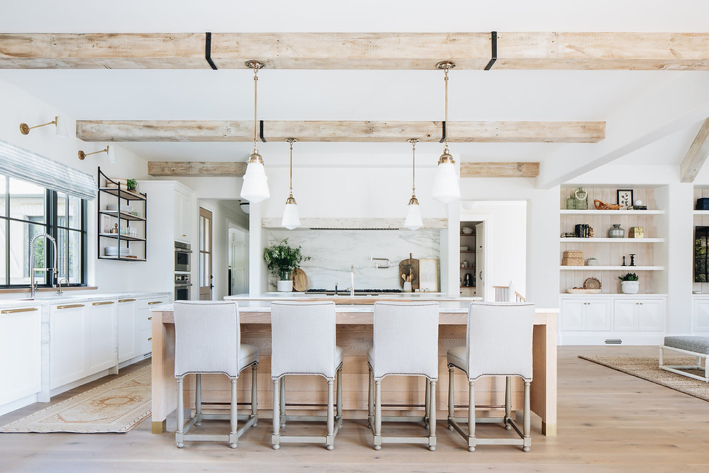 exposed beams with four brass pendant lights marble backsplash pot filler black framed windows open hanging shelves brass sconces four fabric island stools light hardwood floors white cabinets wall oven open shelves in living room