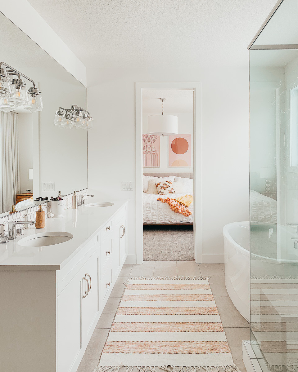 A long white bathroom cabinet and grey floor tiles across from a freestanding tub and blush bath mat that opens to a modern bedroom with pink framed prints on the wall above a white bed.