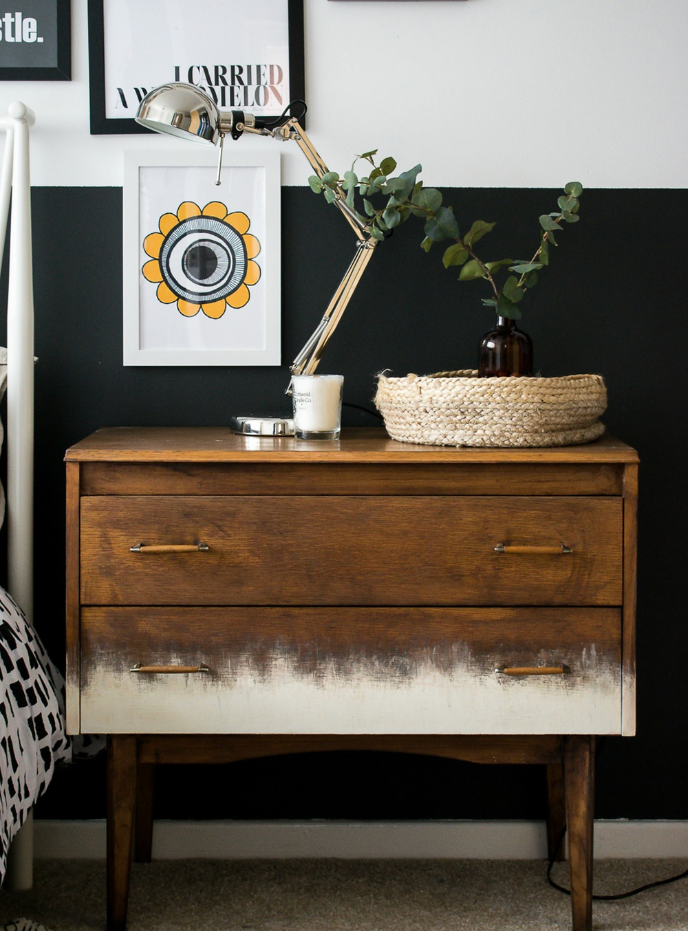 A vintage brown dresser with some distressing beside a bed in a modern home.