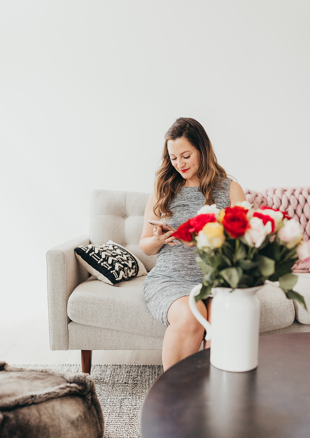 A woman sitting on the couch looking at her phone with a bouquet of flowers on the table in front of her.