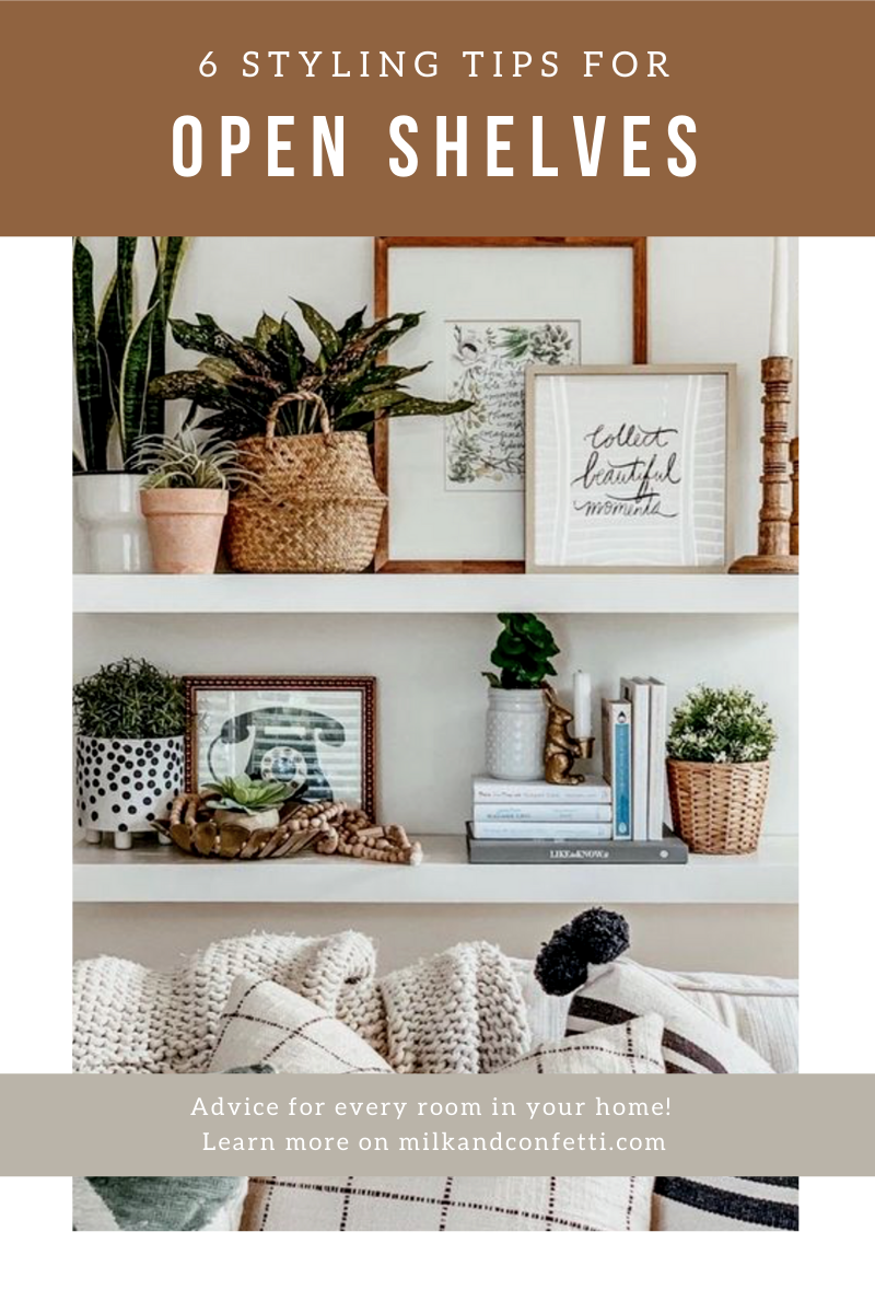 A collection of art and plants styled on some white shelves.
