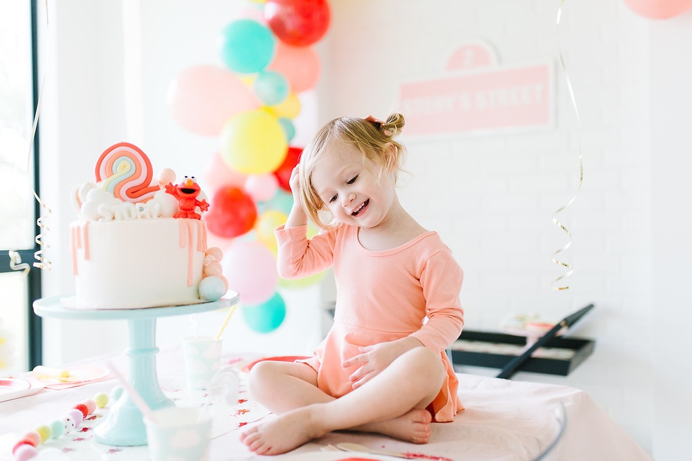 A Sesame Street Elmo birthday party with Elmo tableware, colourful balloons and streamers hanging, a pink Elmo birthday cake, pink wall signage and an Elmo floral centrepiece