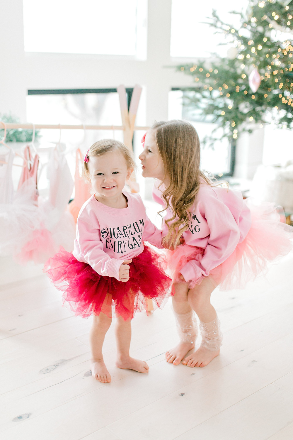 two sisters in pink and red tutu's are dancing together in their sugarplum fairy sweaters in front of a lit Christmas tree.