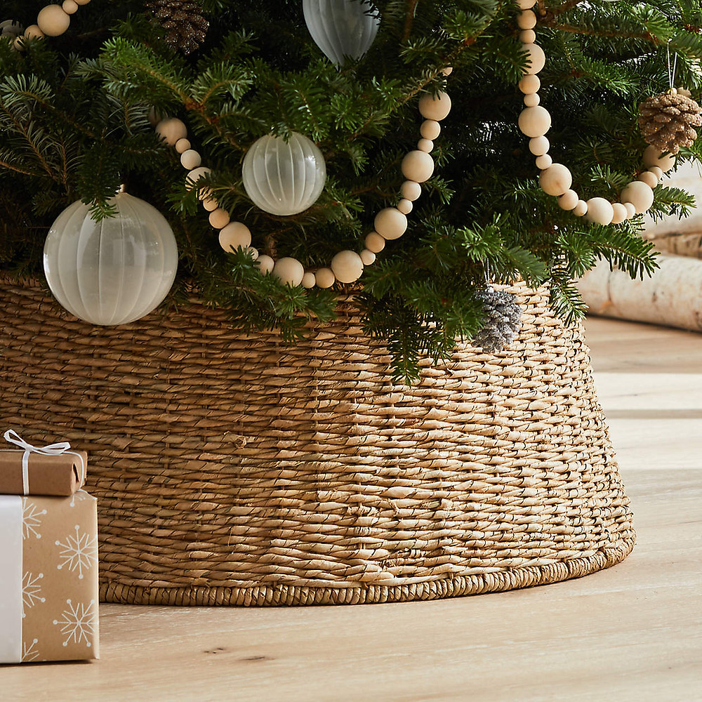 A Scandinavian style Christmas tree sitting in a rattan wicker basket with wooden bead garland and clear glass ornaments is set up for the Christmas holidays.