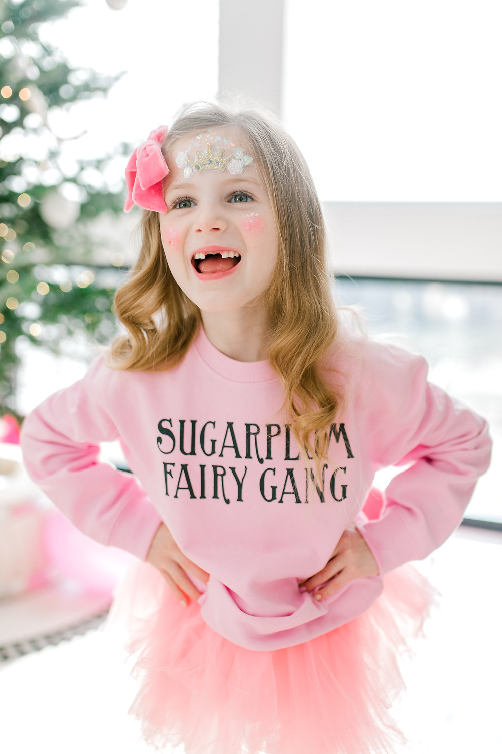 A birthday girl is dressed in a pink hair bow with a pink tutu and a pink sugar plum fairy sweater.