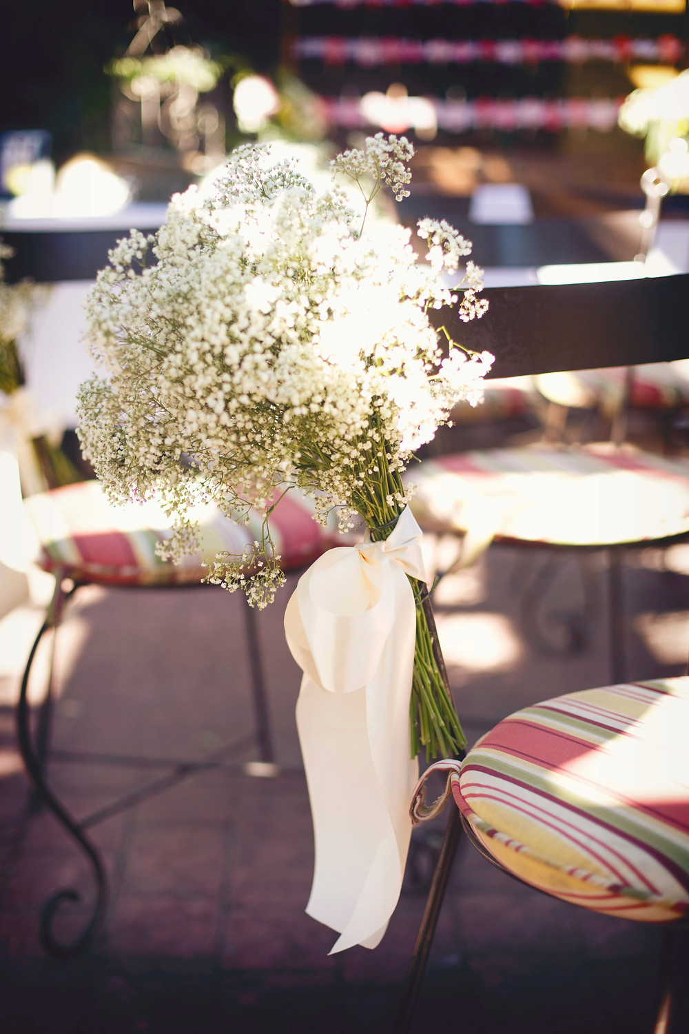 A large bouquet of babys breath tied to a chair with a white satin ribbon at the aisle of an Italian inspired wedding.