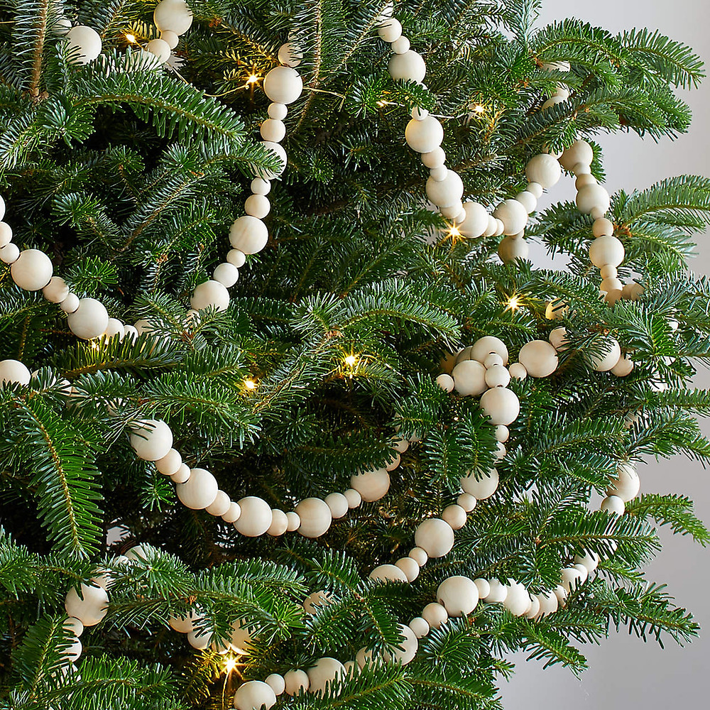 A Scandinavian inspired beaded garland made from natural wood is strung on a green Christmas tree with twinkling lights for a minimal and modern look.