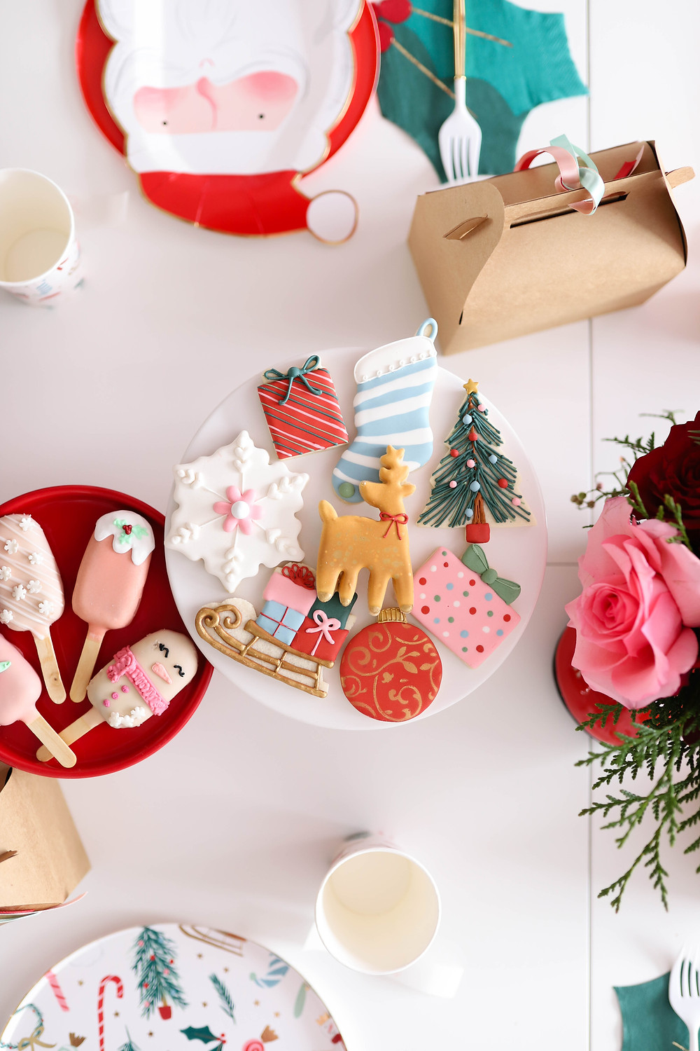 A plate of beautifully decorated christmas cookies on a white table at a kids christmas holiday party in the shape of snowflakes, presents, reindeer, sleighs and a christmas tree.