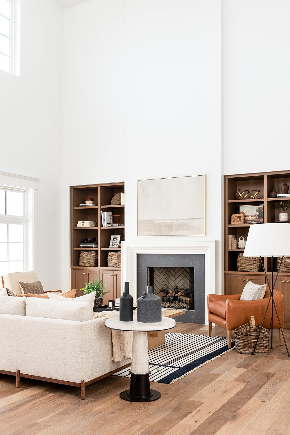 A modern farmhouse living room with a tall white fireplace with a black surround next to some natural wood built in shelves and a white cream sofa with a caramel leather chair.