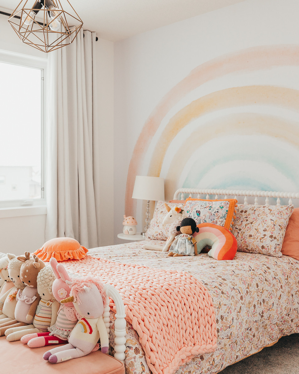 A kids rainbow themed bedroom with colourful floral bedding and a rainbow mural wallpaper on the wall.