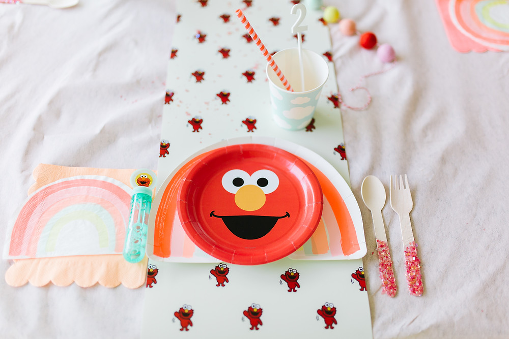 A Sesame Street Elmo birthday party with Elmo plate, Elmo table decor, blue cloud paper cup, paper red strip straw, glitter fork and spoon, bubbles, and rainbow napkin on a white table cloth.