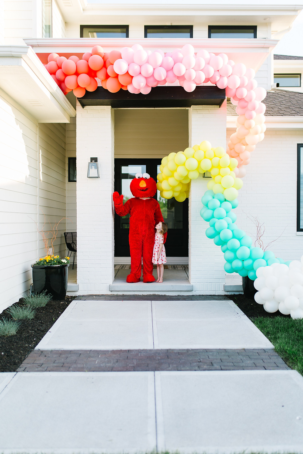 Elmo Birthday party with a colourful balloon garland wrapping the outside of a house.