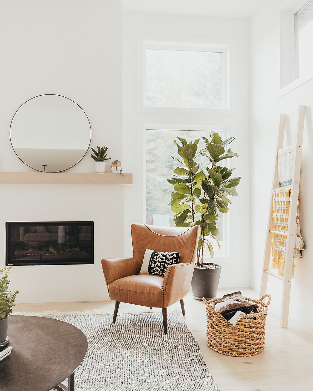 A white Scandinavian living room features light wood oak floors with a natural wool carpet, a brown leather chair, round metal coffee table, a wicker basket with a throw in it, a blanket ladder, a fiddle leaf fig in front of a large window and a linear fireplace with a light wood mantel holding a mirror and some plants.