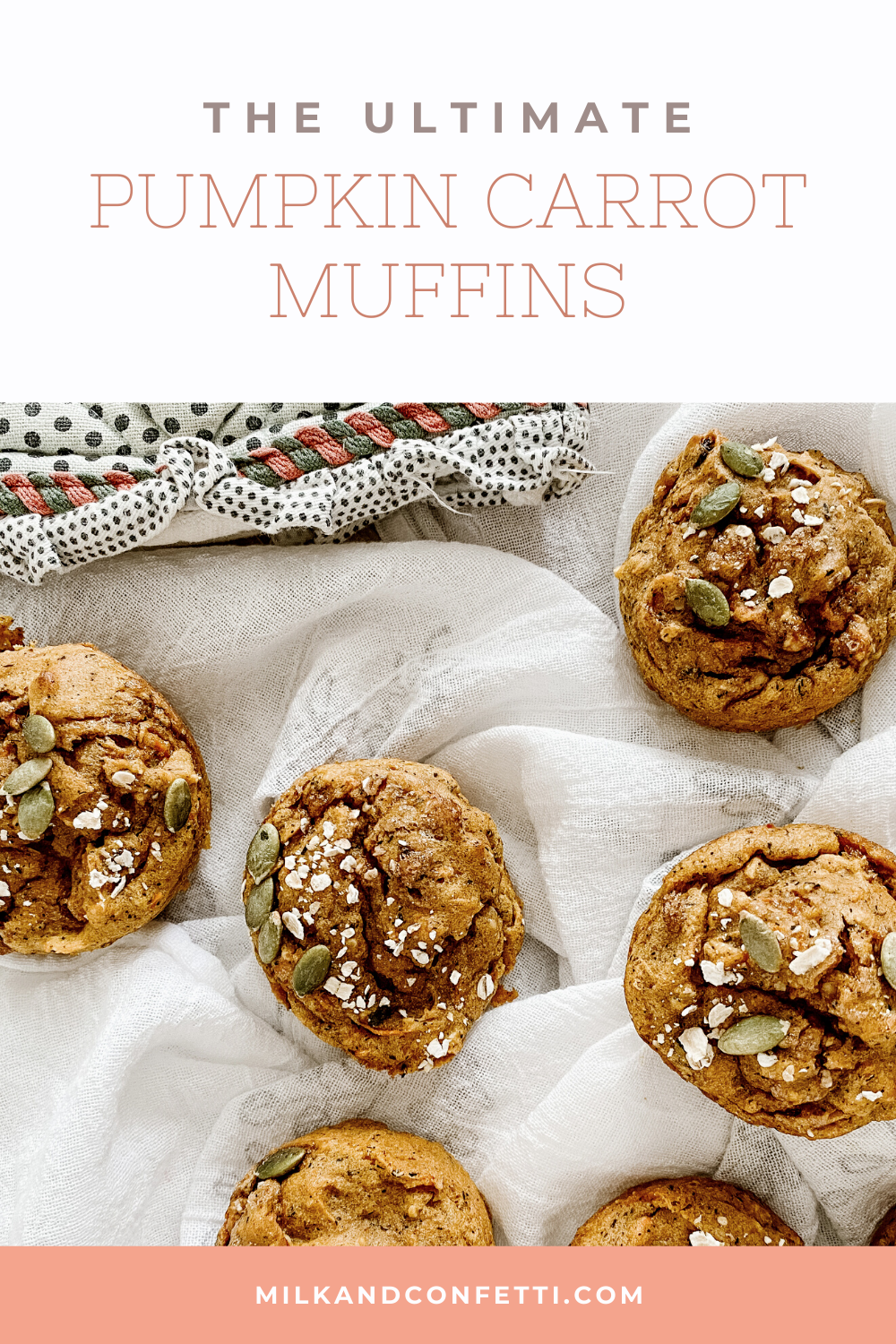 A bunch of carrot and pumpkin muffins sit on a white linen table cloth.