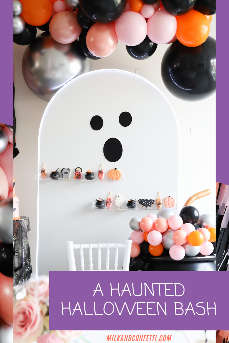 A kids pink, black, and orange halloween party styled with a balloon arch, streams, and a large ghost behind a decorated kids table.