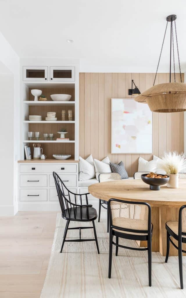 white cabinets with wood shiplap detail round wood table with black framed rattan chair wood black chair throw pillows bench seating black wall sconce pendant light dishes cake stand and books open shelves