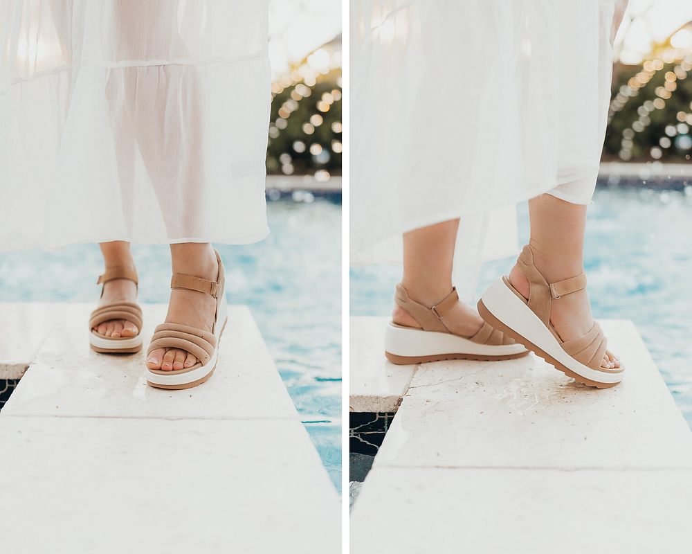 The shoes of a girl standing by the pool in a white dress.