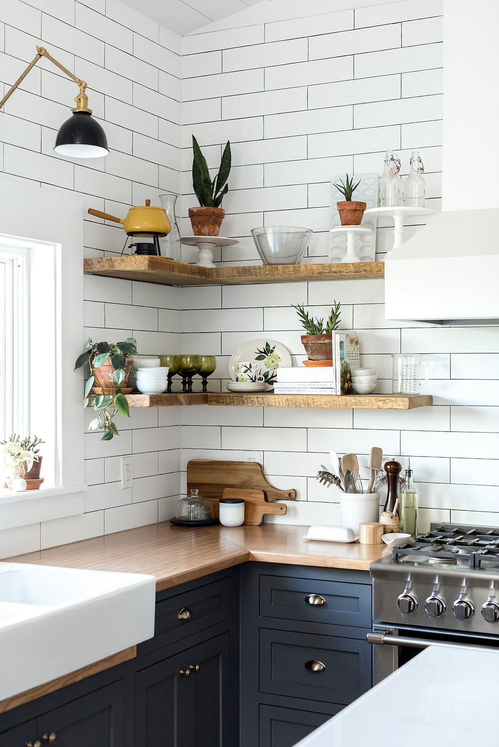 A kitchen with navy blue cabinets and white subway tiles with contrasting grout with open wood shelves displaying some beautiful kitchen accessories.