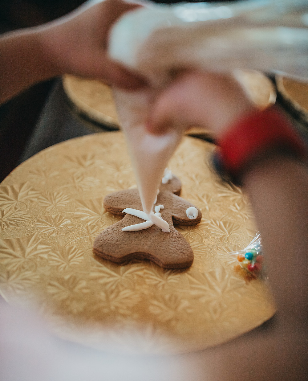 A little girl decorating a gingerbread cookie.