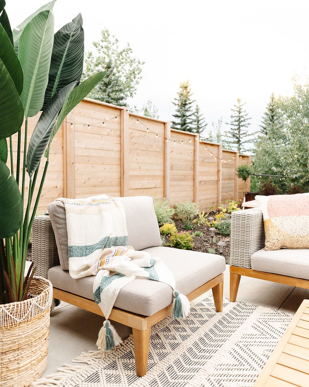 Wicker sofa with wood accents and beige cushions black and white area rug chair with wood accent and striped throw blanket wood accent table with succulent pots wicker basket with blankets patterned oversized pillow on rug potted plant wood fence landscaping perennial flowerbed backyard concrete patio space