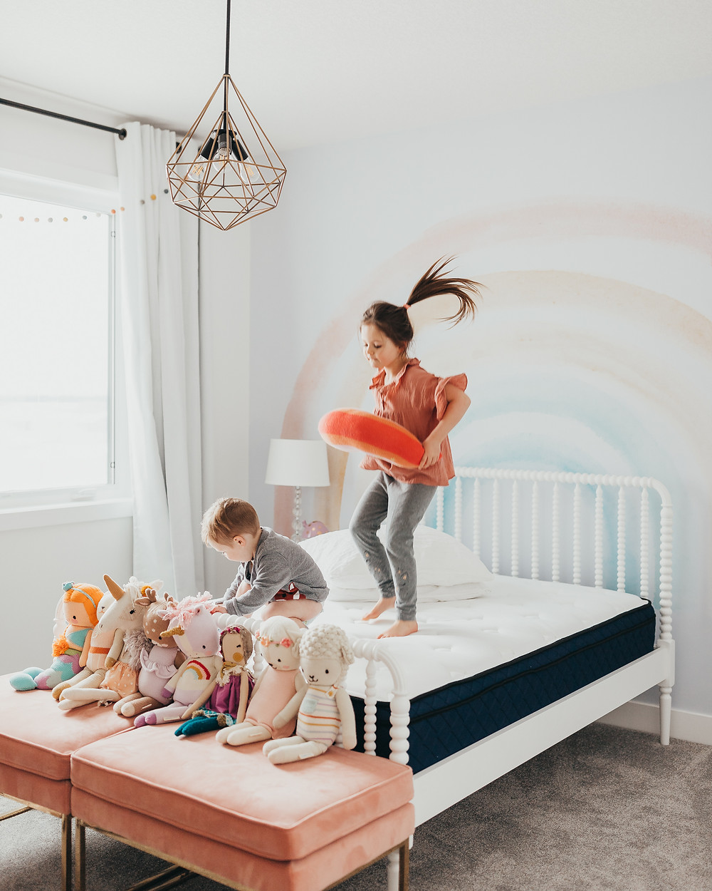 Two kids jumping on a silk and snow mattress in front of a rainbow wallpaper wall.