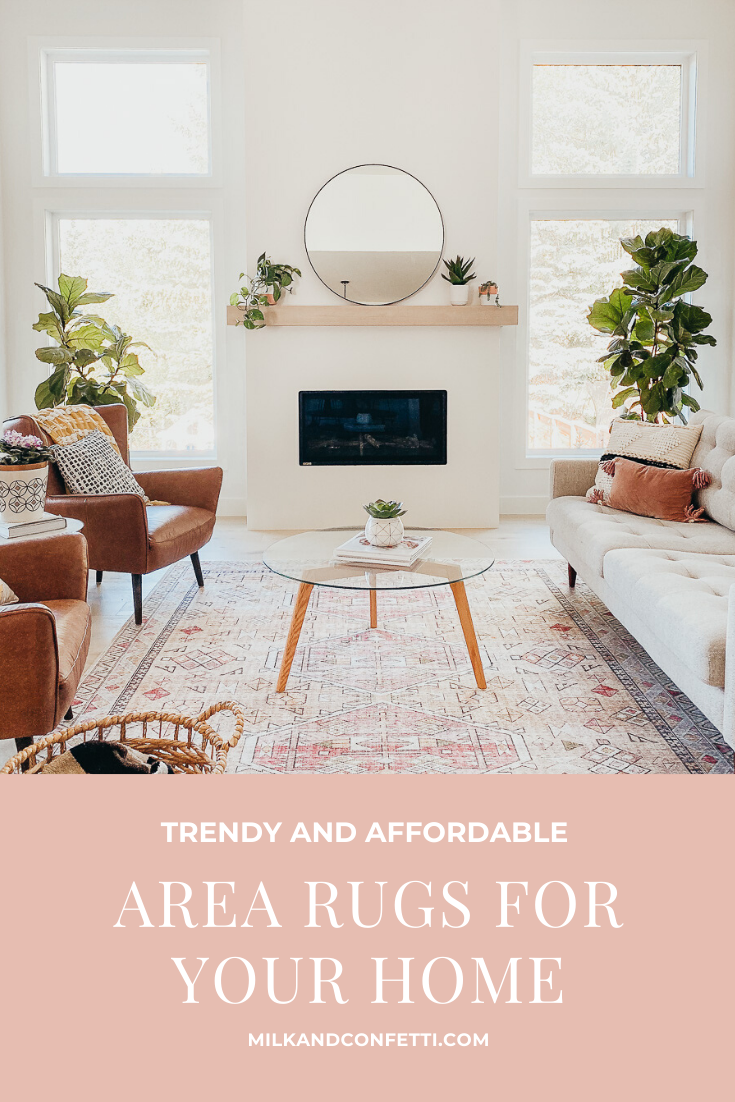 A modern living room with a blush and gold area rug and mid century style furniture.