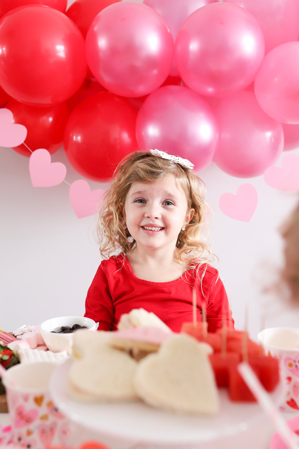 A little girl smiling at the camera at a Valentine's Day party.