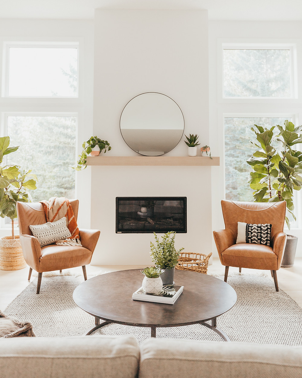two leather armchairs on either side of fireplace wood mantle with round black mirror and plants in pots cream sofa with round wood coffee table with magazine stack and two plants area rug fiddle leaf fig in corner