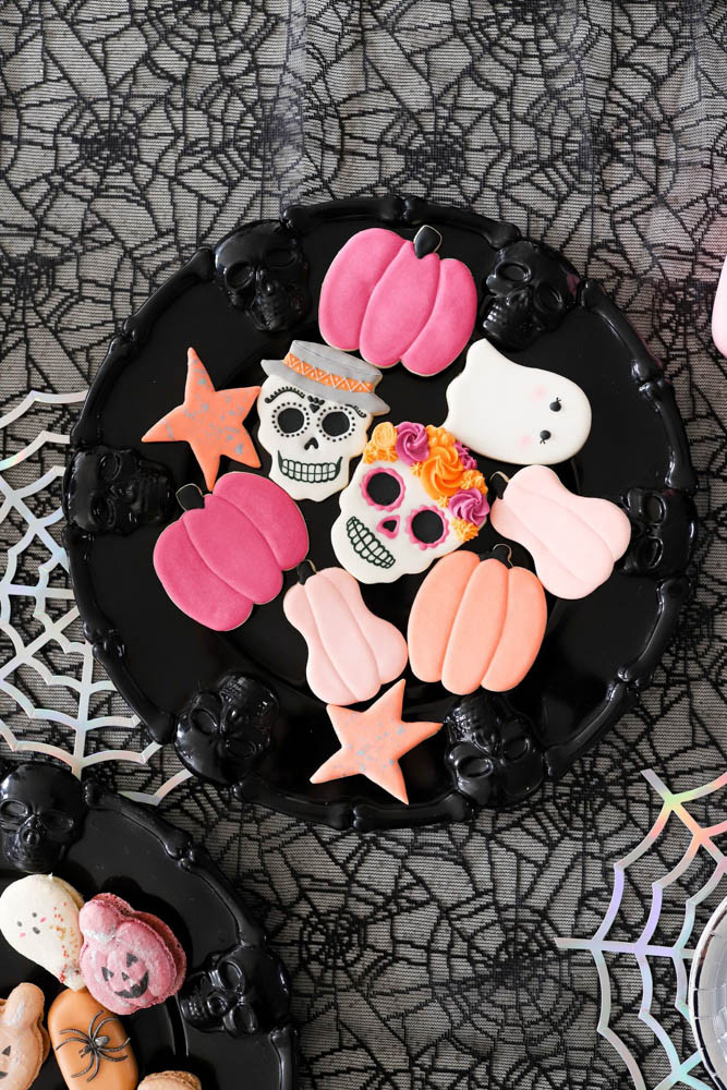 A plate of Halloween pumpkin, skull and ghost cookies sitting on top of a sheer black spider web table cloth at a kids halloween party.