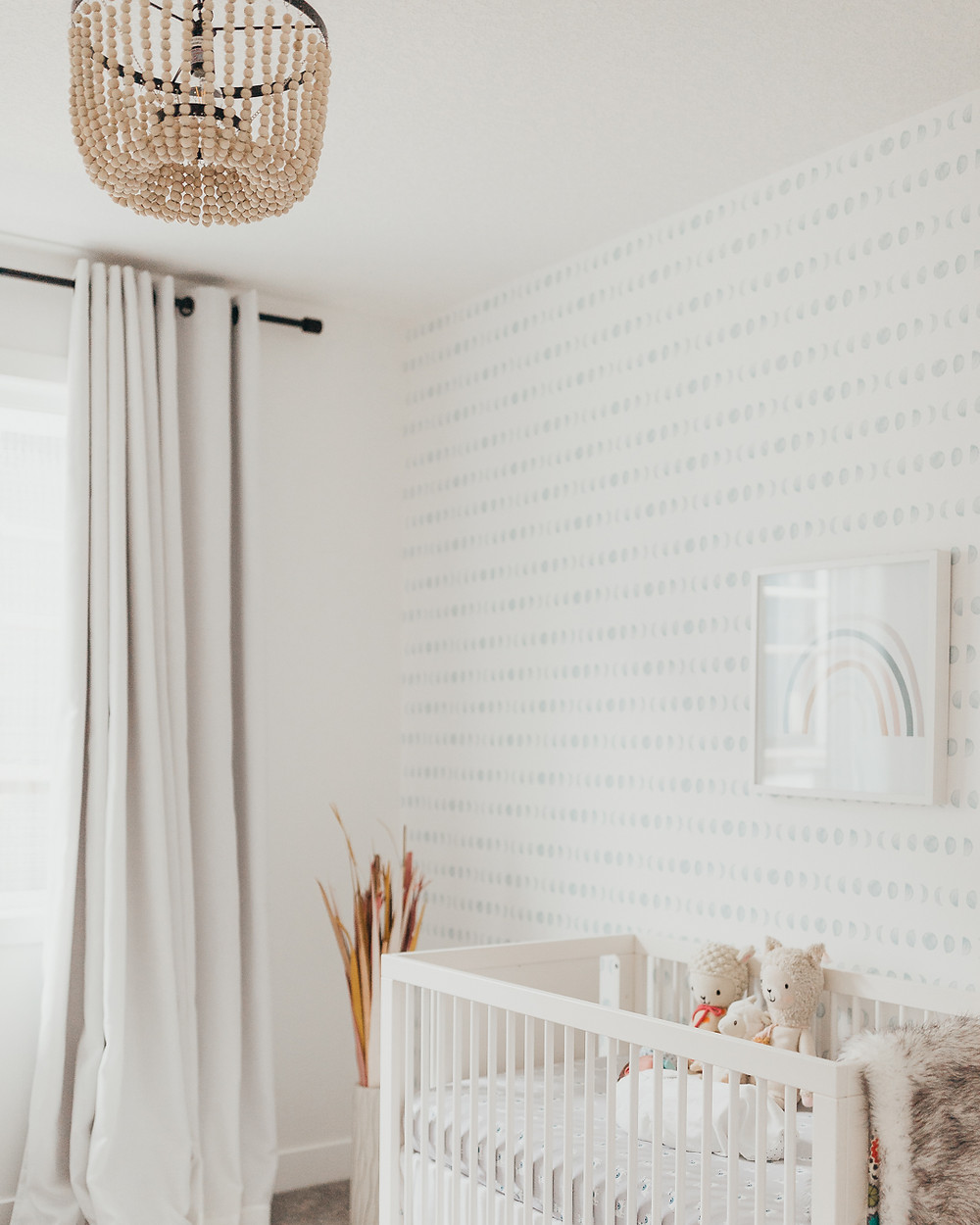 Wood bead chandeilier nursery white crib against wall with rainbow print and blue spotted wallpaper accent cream drapes grasses in vase in corner stuffed animals