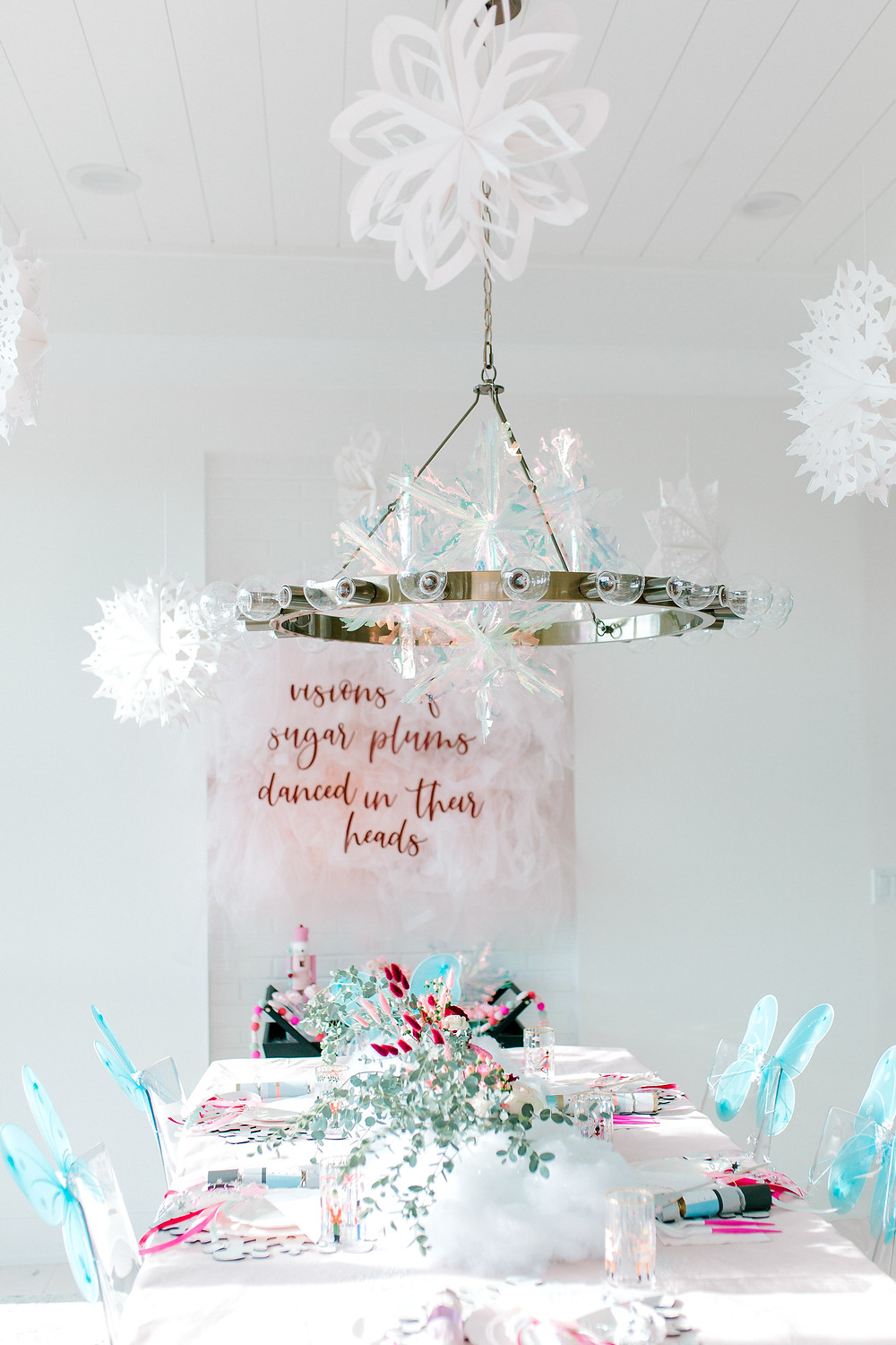 A nutcracker sugar plum birthday party with hanging paper and clear snowflakes and blue butterfly wings with floral centrepieces.