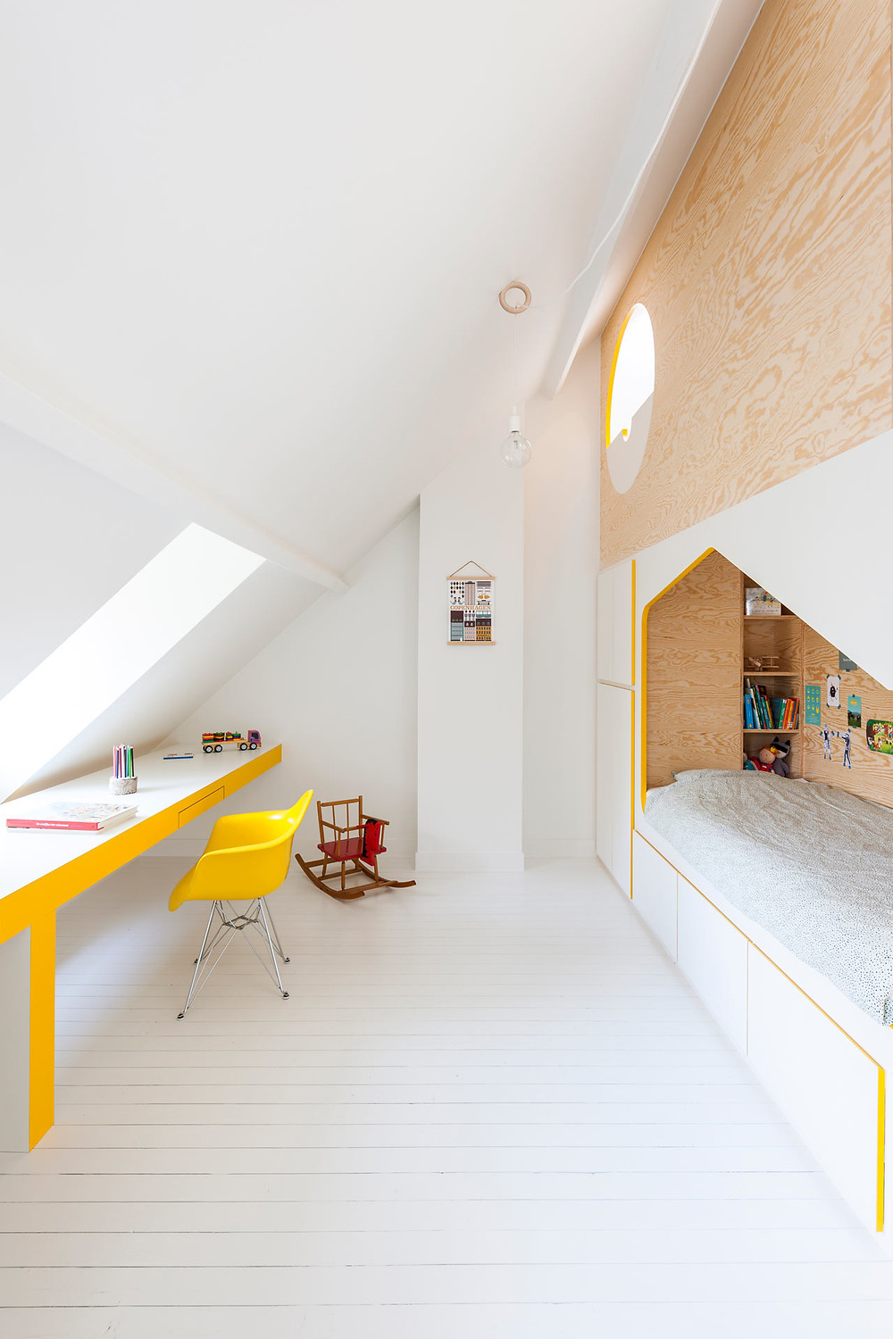 Yellow desk and yellow plastic chair built in daybed with kids books and dolls white walls floor circle porthole window rocking chair