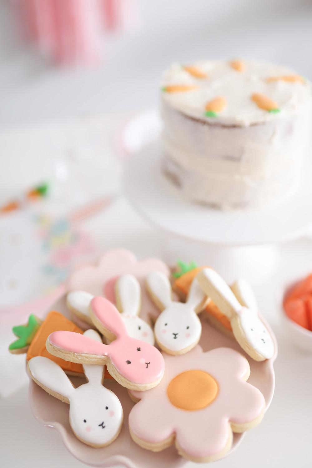 Some beautiful bunny cookies on a pink glass plate ready for an Easter celebration.