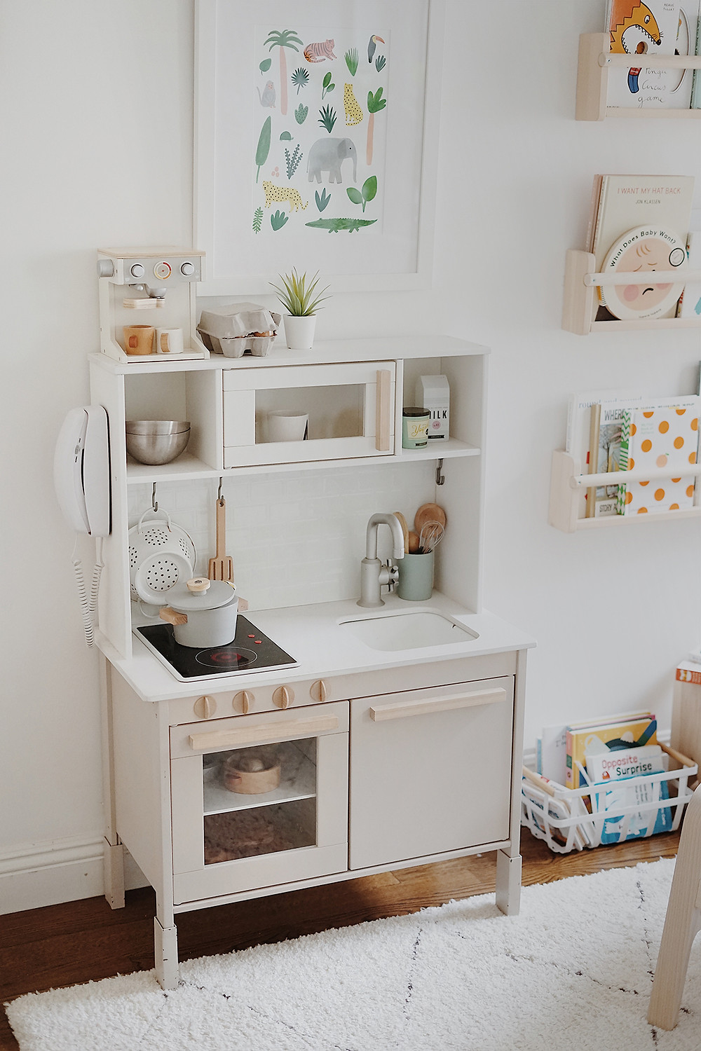 A childrens white IKEA play kitchen in simple white playroom with a patterned neutral area rug and bookshelves