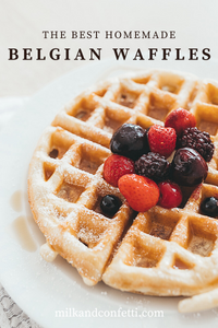 A homemade belgian waffle topped with berries and syrup on a white plate.