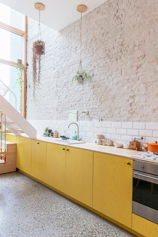 Yellow kitchen cabinets no upper cabinets exposed brick wall two hanging plants under counter stove single sink orange le cruset pot spice pots kids step stool