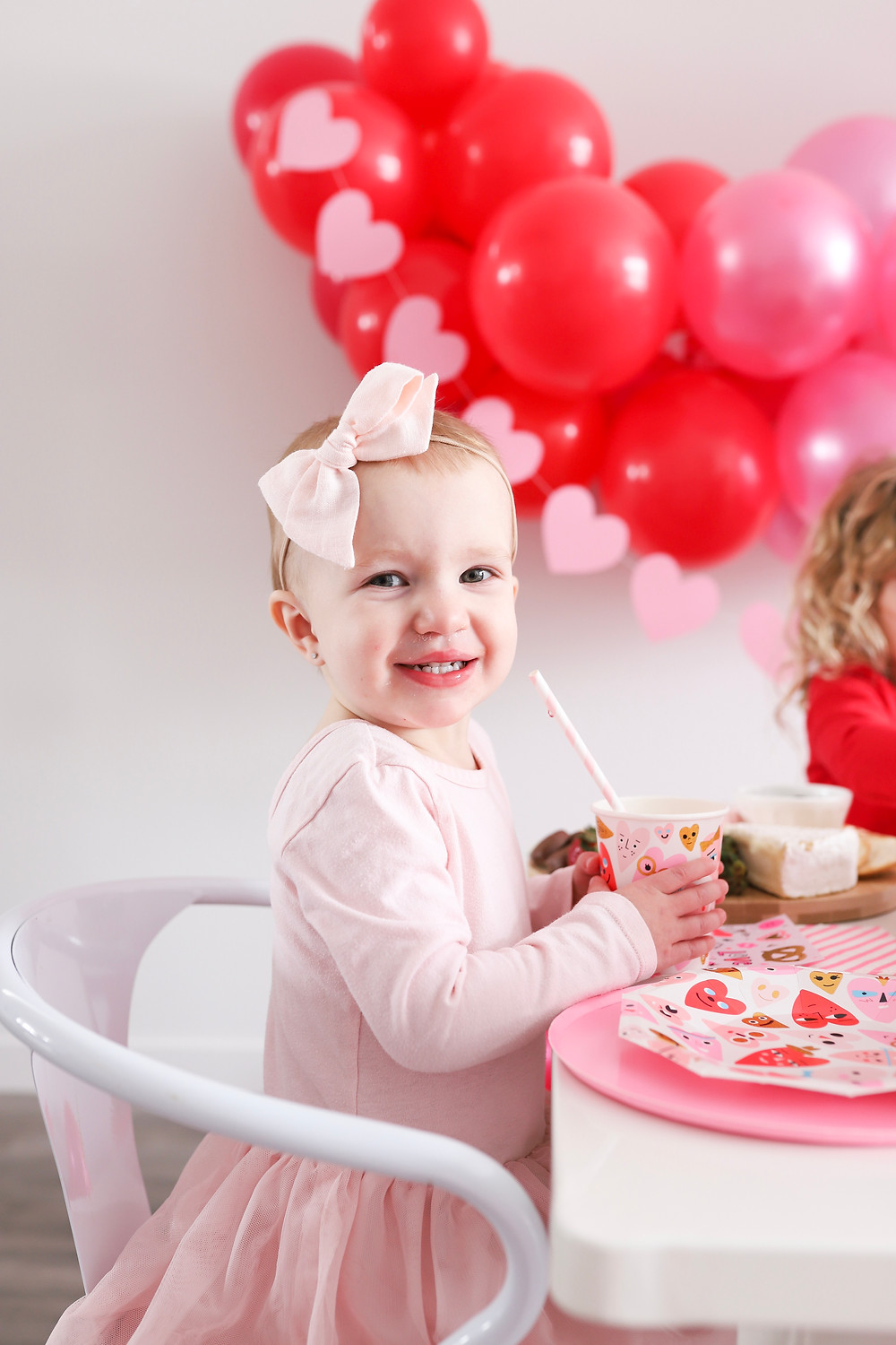 A little girl smiling at the camera holding a cup at a Valentine's Day party.