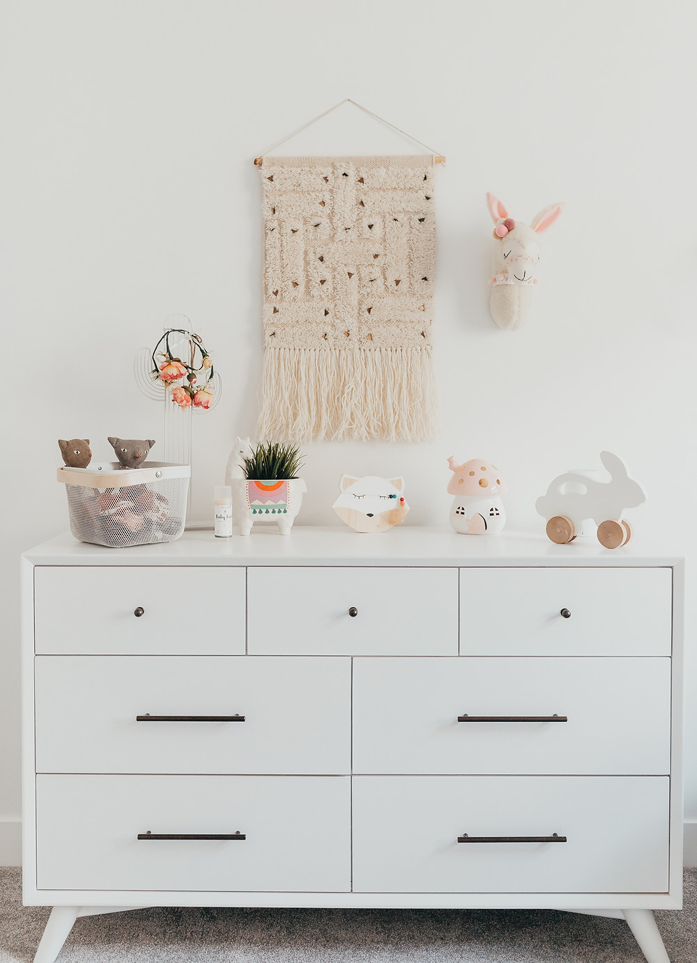 A white dresser in a baby nursery with a wall tapestry hung above.
