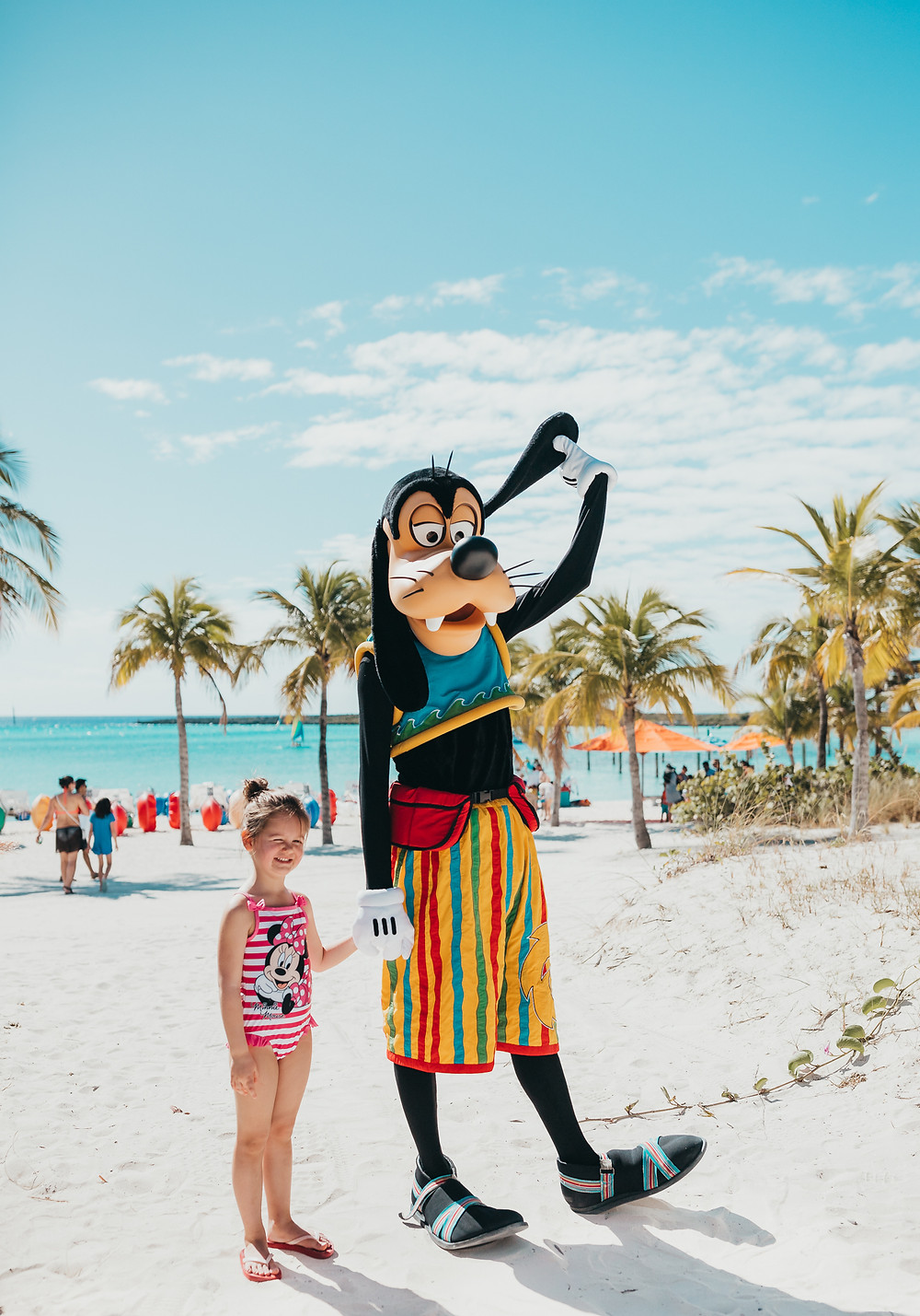 A little girl wearing a Minnie Mouse bathing suit standing with Goofy on the beach.