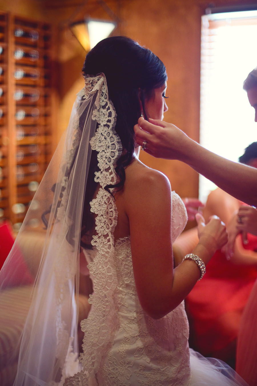 A bride on her wedding day wearing a lace veil getting ready to walk down the aisle.