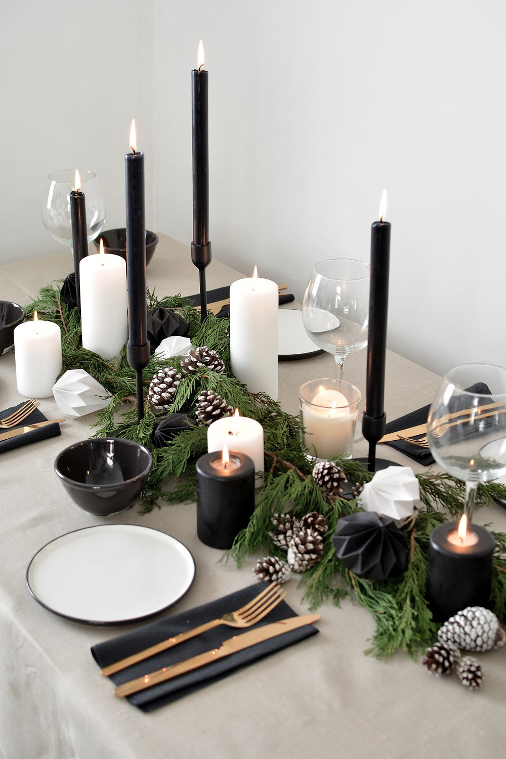 A minimal and modern Scandinavian nordic inspired Christmas holiday dining table styled with black candles, greenery, white candles, pine cones and black plates with gold utensils for a minimal and modern feel.