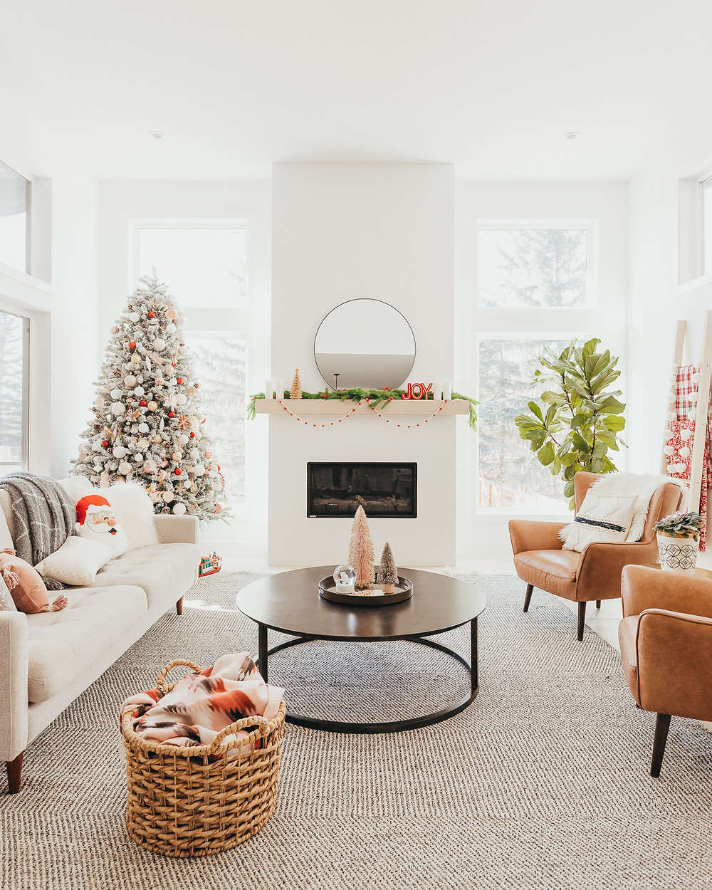 A modern scandinavian living room decorated for the Christmas holidays with a flocked christmas tree next to a white fireplace, some bottle brush trees on a black table and a grey sofa with some Santa pillows.