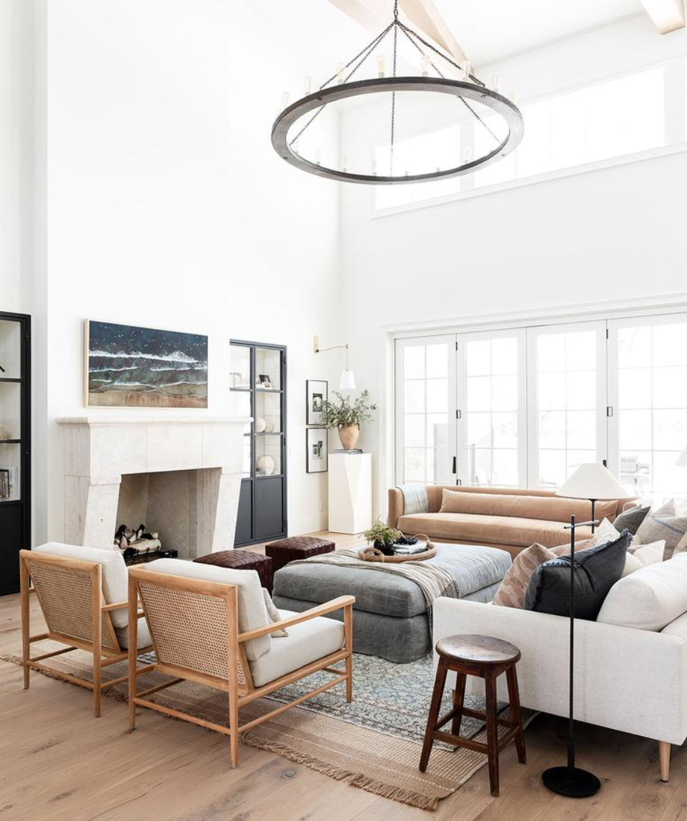 A modern living room with a white stone fireplace styled with some minimal white chairs, a brown leather sofa and a grey ottoman beneath a round chandelier.