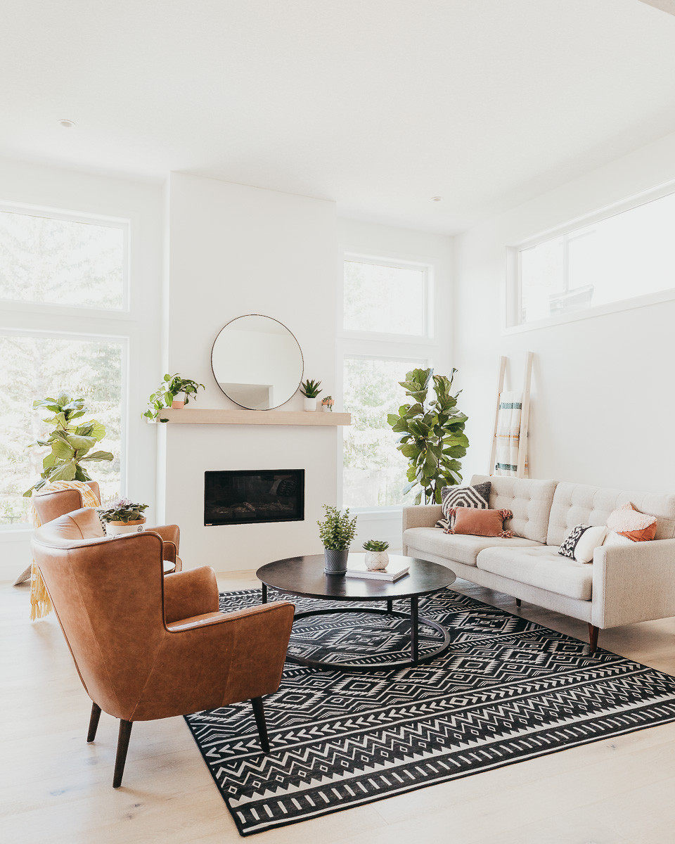 A mid century modern living room with a black aztec area rug, brown leather chairs and a grey sofa in front of a  linear white fireplace with a white oak mantle.