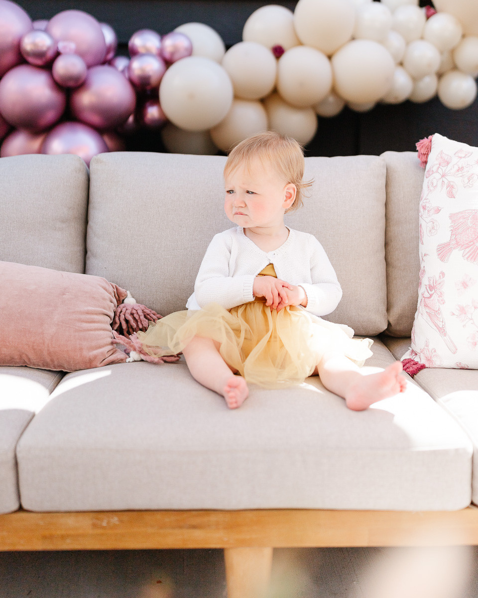 A little girl who just turned one is sitting on a sofa at her first birthday in front of a purple balloon arch.