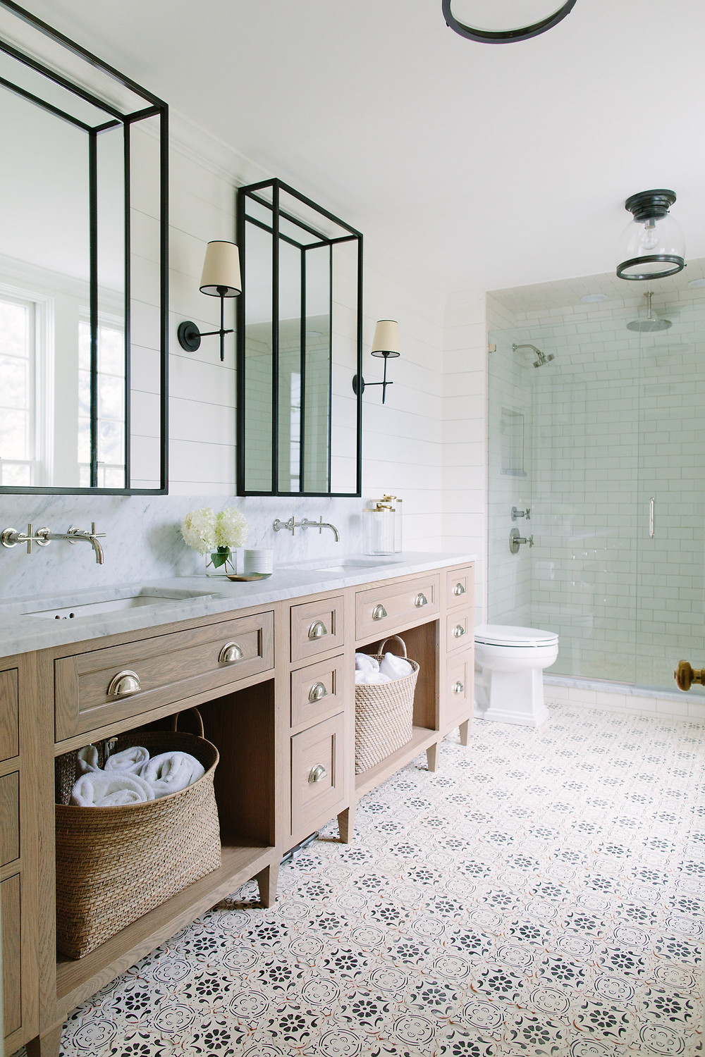 marble countertop concrete patterned tile floor bathroom wood double sink vanity open storage baskets with towels wall mounted hardware black framed mirrors wall sconces walk in tile shower subway shiplap walls nautical light fixture