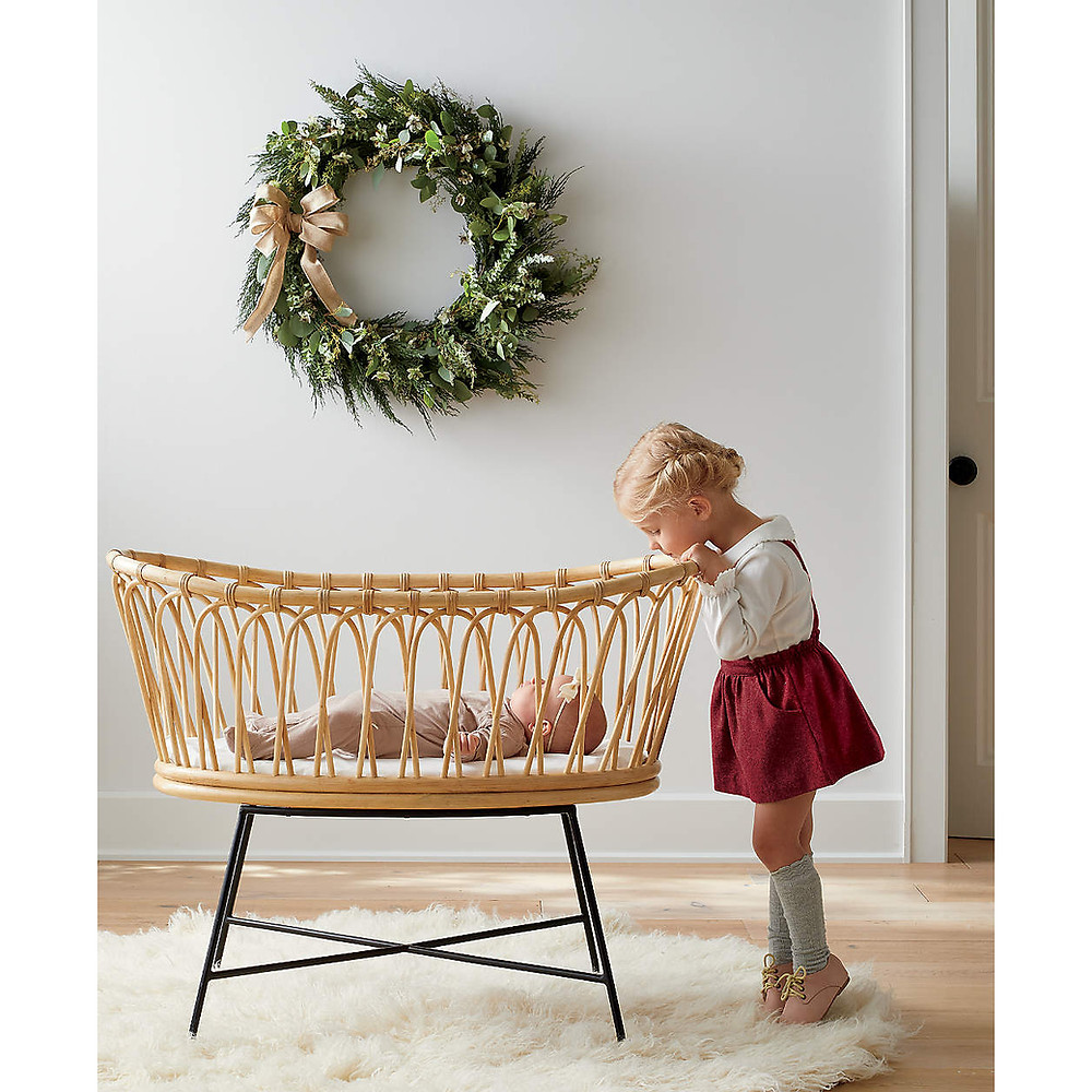 A little girl in a red skirt and knee socks leans over a wicker Scandinavian inspired bassinet sitting on a white fur rug looks at her baby sister in front  of a simple and modern wreath that hangs on the wall behind her.