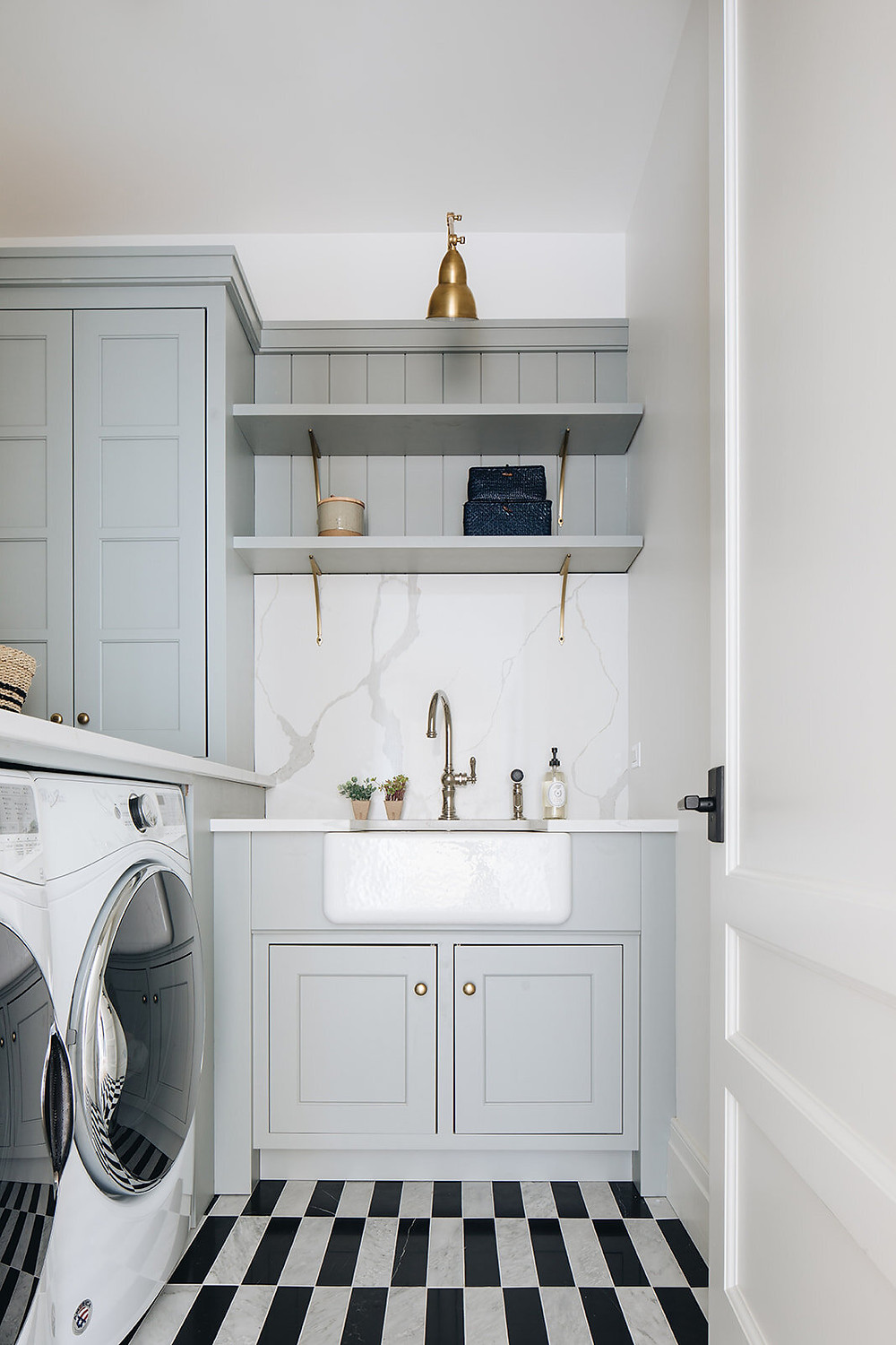 laundry room with black and white rectangular floor tiles farmhouse sink brass hardware storage brass sconces white door front load washer and dryer countertop